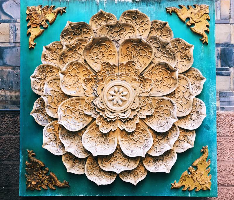 在墙壁上的花卉样式石头塌落装饰 库存图片