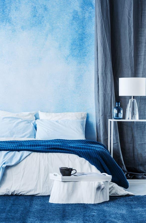 在墙壁上的蓝色水彩油漆在现代卧室内部机智 免版税库存照片