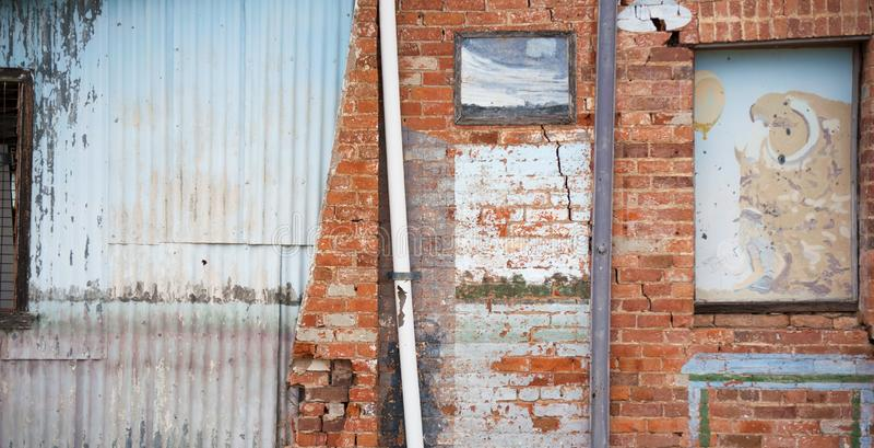 在墙壁下的老奔跑由砖和波状钢制成 库存图片