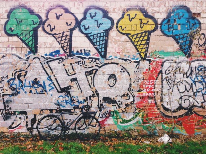 在墙壁前面的灰色黑fixie自行车有冰淇凌街道画的 库存照片