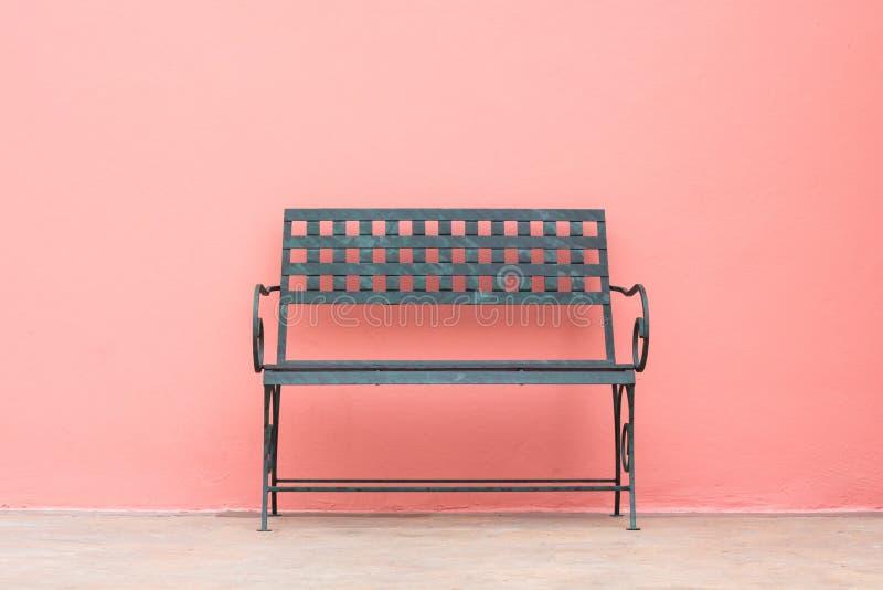 在墙壁前面的铁椅子 免版税库存图片