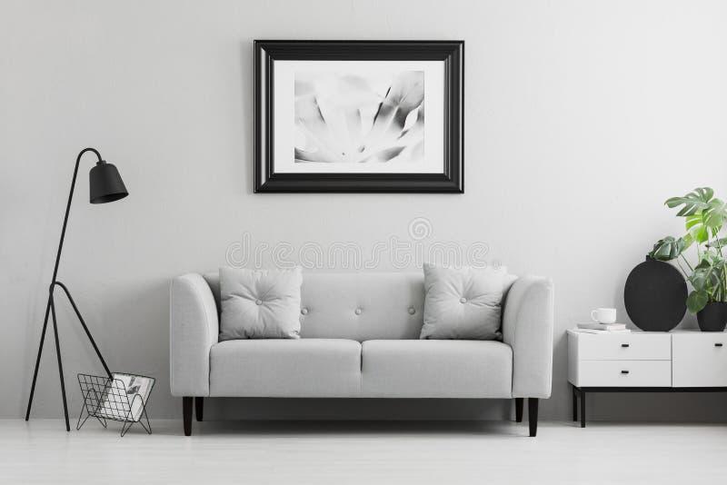 在墙壁在花梢上,灰色沙发有坐垫的在最低纲领派客厅内部和地方上的被构筑的照片桌的 真正的pho 免版税库存图片
