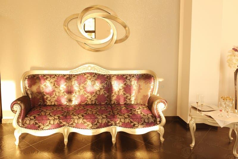 在墙壁旁边的美丽的葡萄酒沙发 免版税库存图片