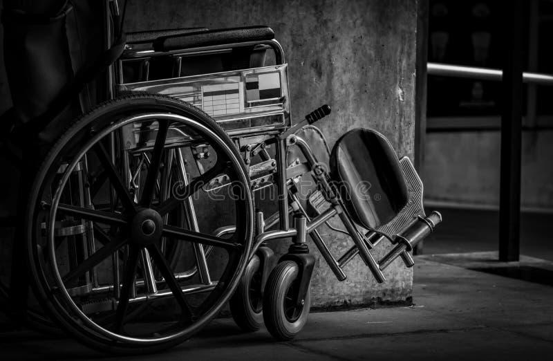 在墙壁旁边被折叠的轮椅 在医院概念的哀伤的新闻 与老化社会的消沉 偏僻的空的轮椅 免版税库存图片