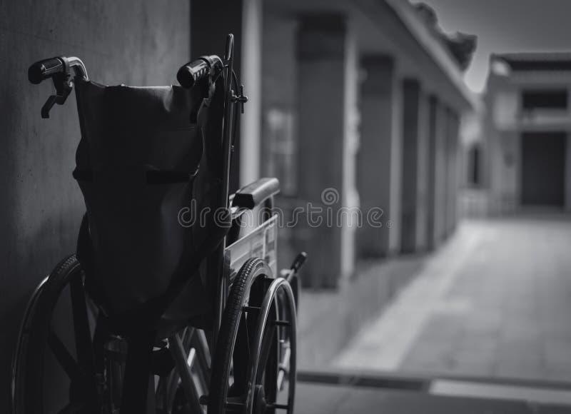 在墙壁旁边被折叠的轮椅 在医院概念的哀伤的新闻 与老化社会的消沉 偏僻的空的轮椅 图库摄影
