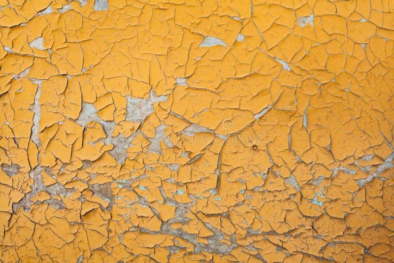 在墙壁无缝的纹理的削皮油漆 土气黄色难看的东西材料的样式 图库摄影