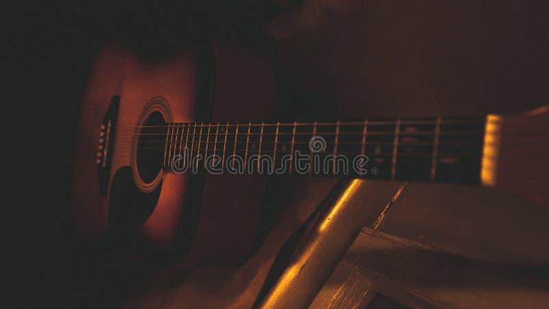 在墙壁的老声学吉他 库存图片