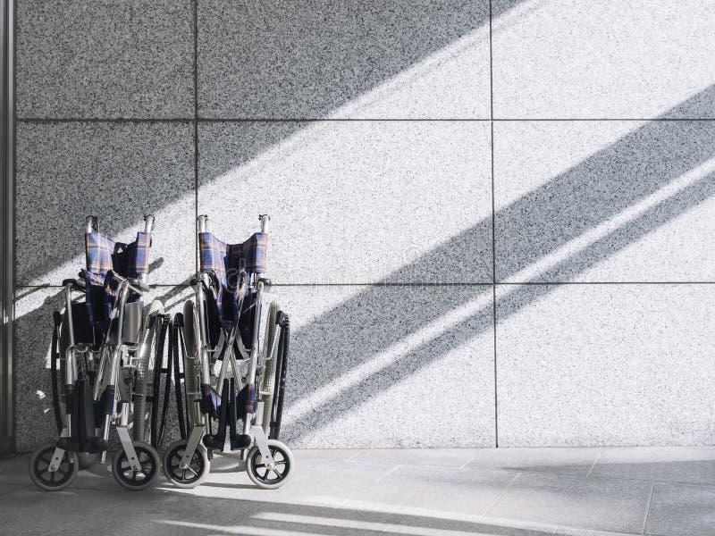 在墙壁背景的空的轮椅与阴影照明设备 免版税库存照片