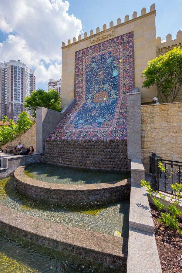 在墙壁附近的一个小装饰落下的喷泉,描述一张阿塞拜疆地毯 库存照片