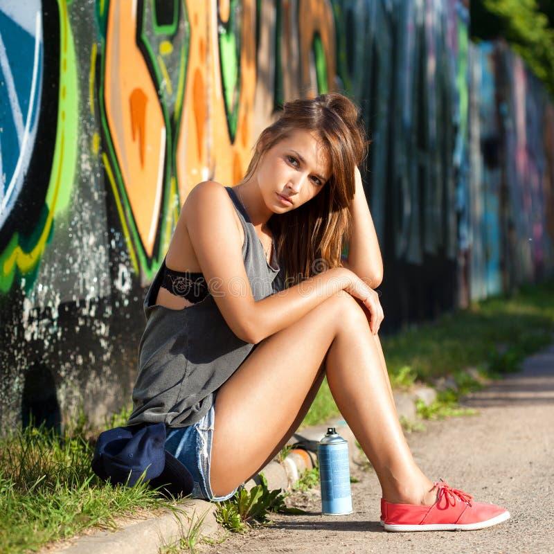 在墙壁附近的女孩有街道画的 免版税库存照片
