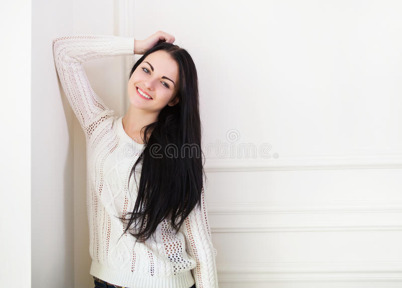 在墙壁附近的愉快的逗人喜爱的青少年的女孩在屋子里 图库摄影