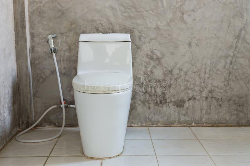 在墙壁附近的白色马桶在卫生间里 免版税库存照片