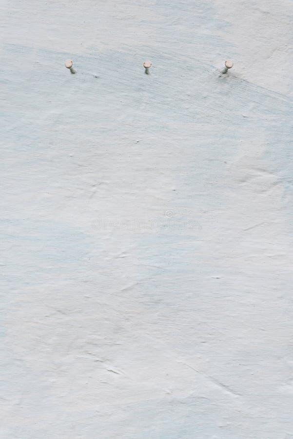 在墙壁,土坯房,减速火箭的样式,在白色的织地不很细背景被粉刷的墙壁的钉子  库存图片