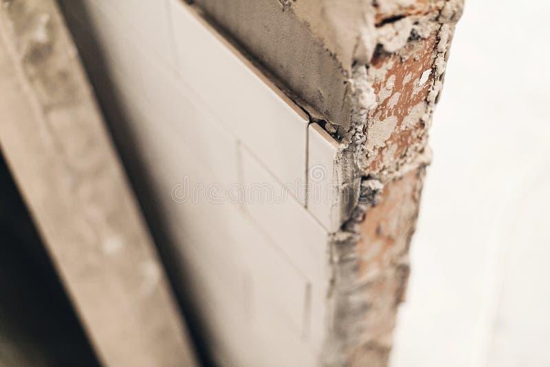 在墙壁,整修概念上的现代白色瓦片 陶瓷ceranic纹理瓦片 库存图片