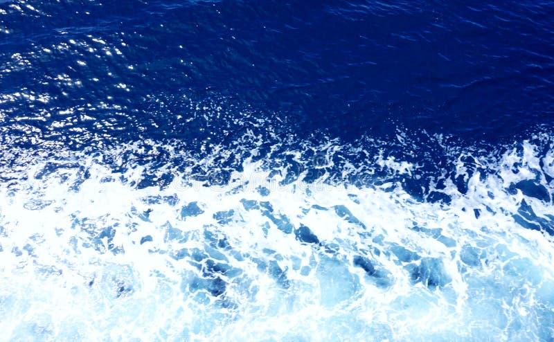 在墨水蓝色口气和白海泡沫,顶视图的起波纹的海水 免版税库存照片