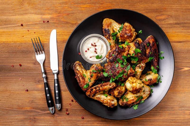 在墨西哥人有咖喱调味料的和荷兰芹的被烘烤的鸡翅在一个黑色的盘子,在木背景 侧视图,拷贝空间 库存图片