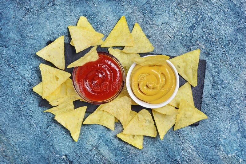 在墨西哥烤干酪辣味玉米片芯片的在白色碗的顶视图与辣红色和乳酪调味料或者垂度 免版税库存图片