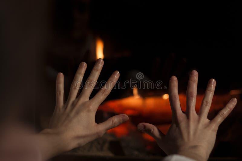 在壁炉前的准备手 温暖的房子 免版税库存照片