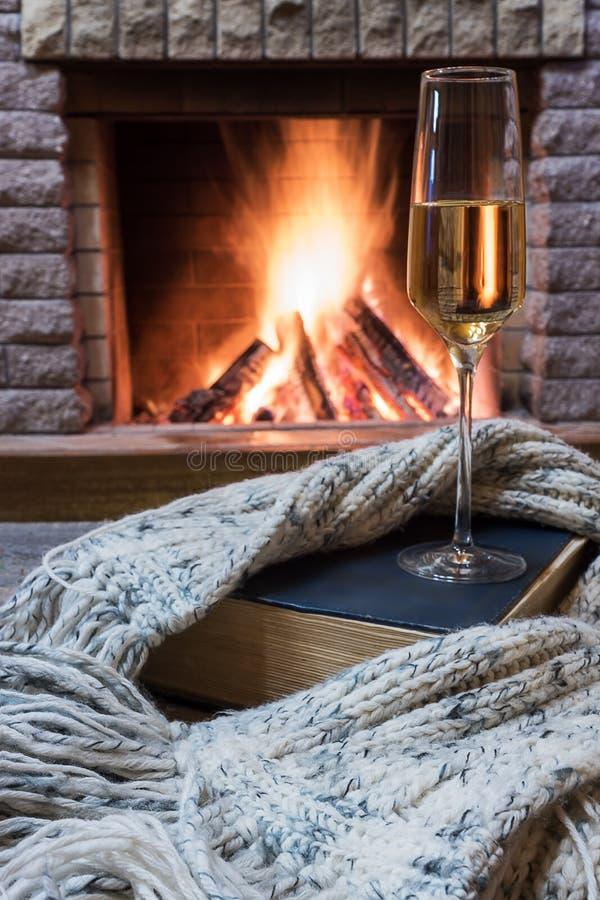 在壁炉前的舒适场面与杯酒、书和羊毛温暖的围巾 图库摄影