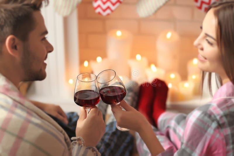 在壁炉前面的夫妇饮用的酒在家 免版税库存照片