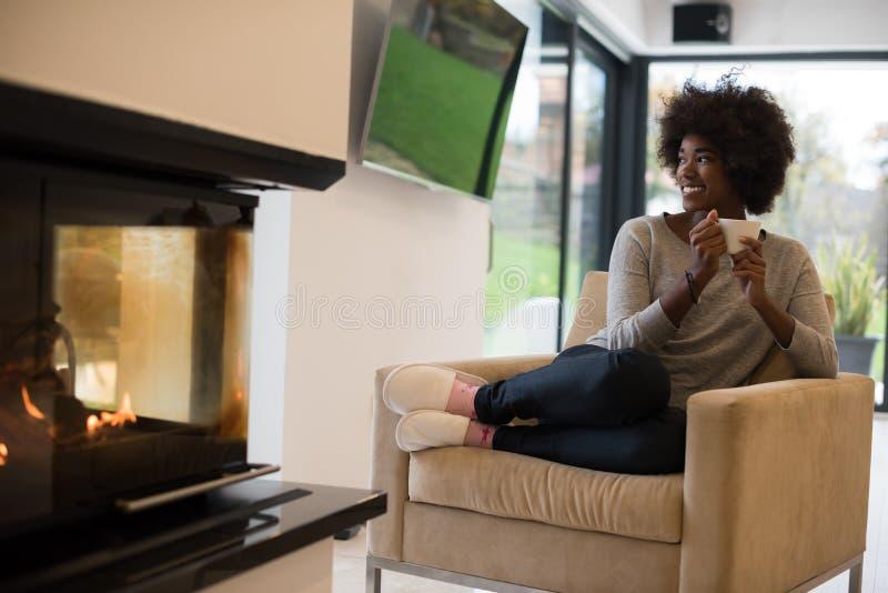 在壁炉前面的黑人妇女饮用的咖啡 免版税库存图片