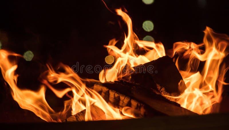 在壁炉的火与在黑背景的五颜六色的火焰 关闭与细节,空间 免版税库存图片