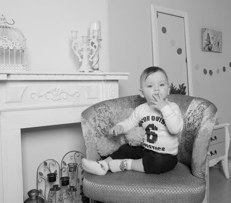 在壁炉附近在客厅,椅子的孩子,黑白 库存照片