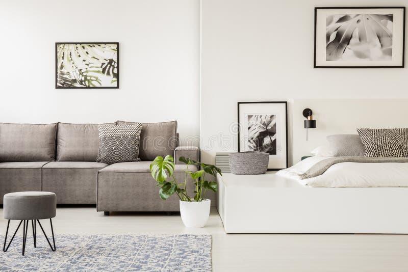 在壁角沙发前面的灰色凳子在露天场所内部与 免版税图库摄影