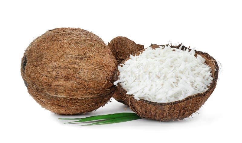 在壳的被磨碎的椰子和在背景的整个坚果 库存图片