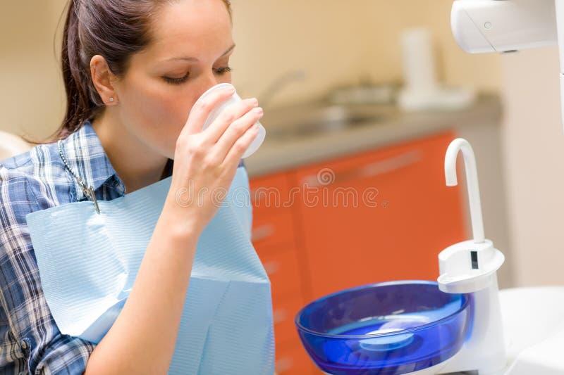 在处理以后的牙齿耐心的妇女洗涤嘴 免版税库存图片