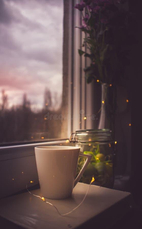 在复活节早晨、咖啡、书、复活节彩蛋和花的日出在窗口 免版税库存照片