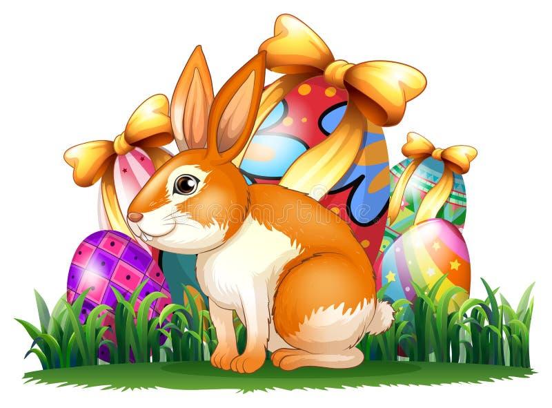 在复活节彩蛋前面的一个逗人喜爱的兔宝宝 皇族释放例证