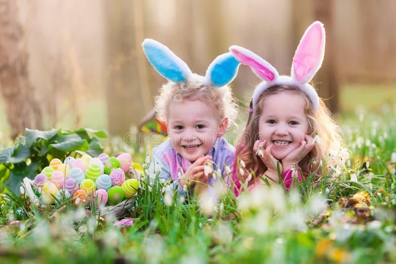 在复活节彩蛋的孩子在开花的春天庭院里寻找 免版税库存图片