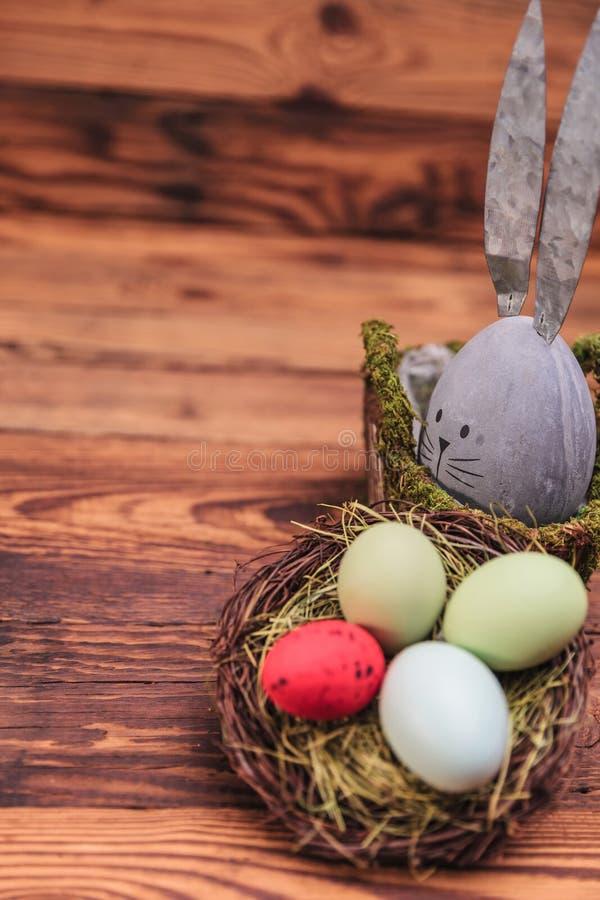 在复活节彩蛋篮子附近的逗人喜爱的具体鸡蛋兔子形象 库存图片
