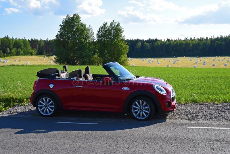 在夏令时期间的微型cabrio在countryroad旁边停放了 图库摄影