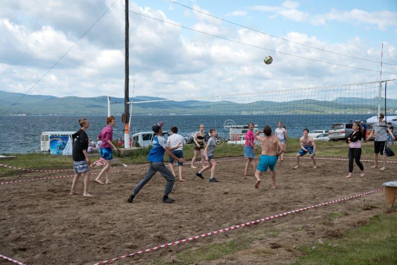 在夏天休假期间,少年打在海滩的排球,在一个大湖的岸 免版税库存图片