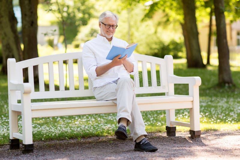 在夏天公园的愉快的老人阅读书 免版税图库摄影