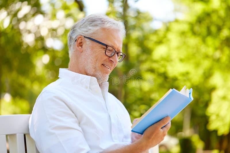 在夏天公园的愉快的老人阅读书 免版税库存图片