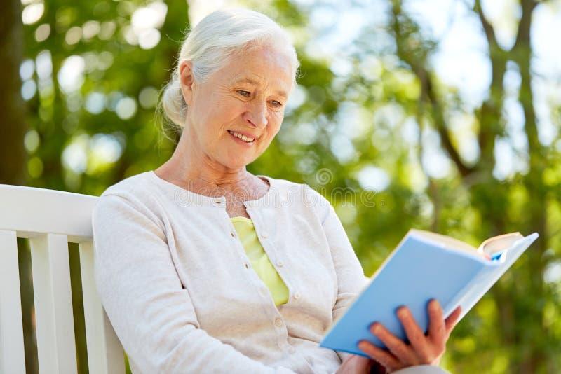 在夏天公园的愉快的资深妇女阅读书 库存图片
