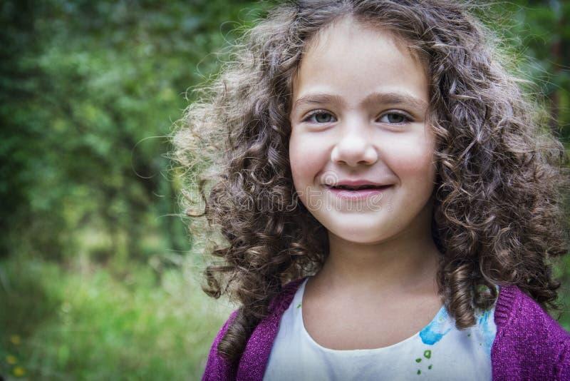 在夏天在公园有一个小卷曲微笑的女孩 免版税库存照片