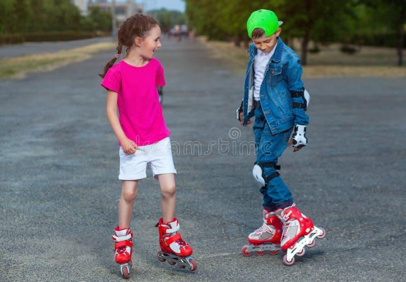 在夏天在公园,男孩和女孩在溜冰鞋滚动 免版税库存照片