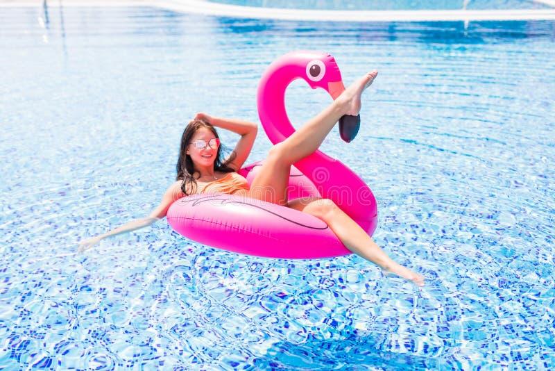 在夏天塑造一个年轻和性感的女孩的画象水池的在游泳衣和太阳镜的一群可膨胀的桃红色火鸟 P 免版税库存照片