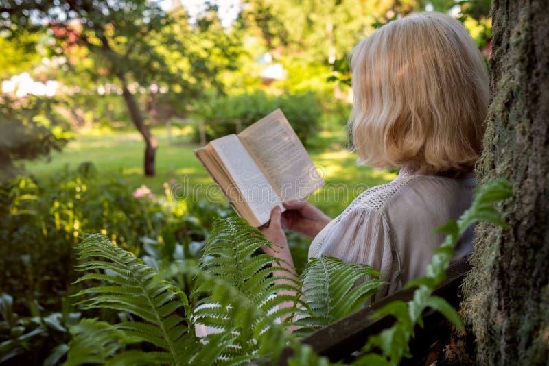 在夏天庭院里读书的资深妇女坐在树附近 免版税库存照片