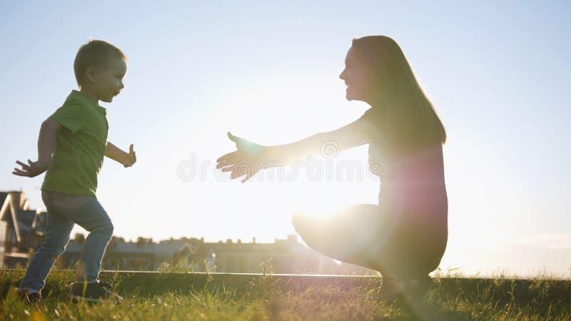 在夏天日落公园-跑到妈妈的孩子照顾与儿子的戏剧 免版税库存图片