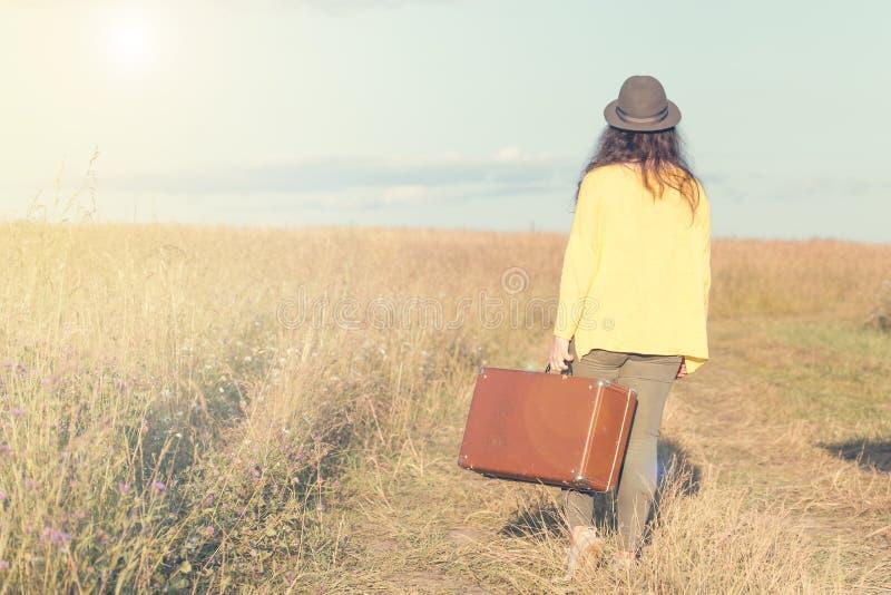 在夏天日落期间,有黑帽会议的美丽的少妇运载在领域路的棕色葡萄酒手提箱 回到视图 被定调子的图象 库存图片