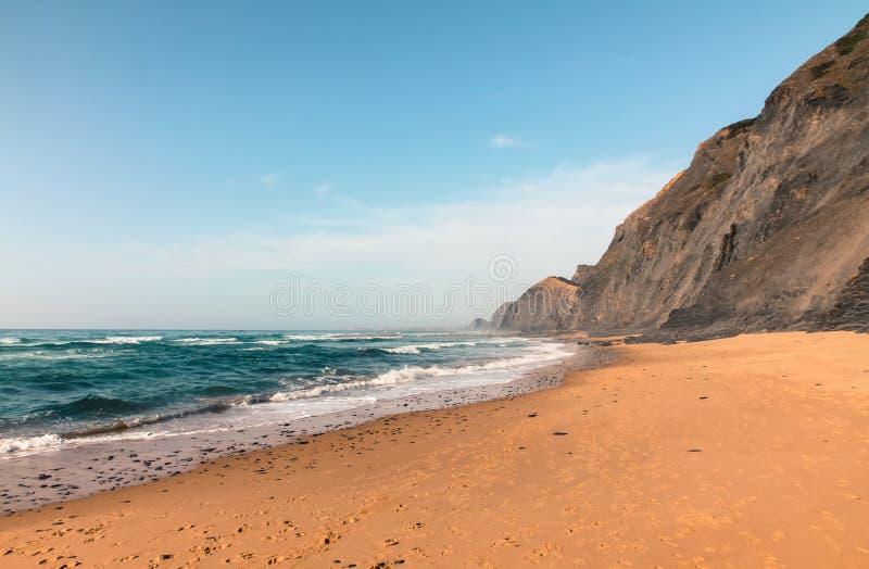在夏天期间,一个离开的海滩用火山的峭壁和大西洋的蓝绿色水在萨格里什, Algarves,葡萄牙 图库摄影
