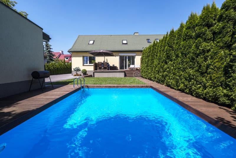 在夏天期间,游泳池在房子庭院里有树的 r 免版税库存照片
