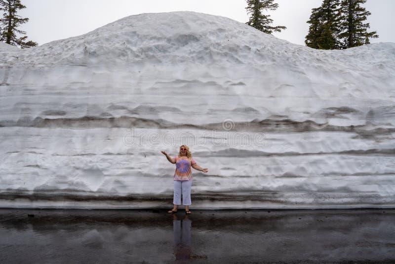 在夏天期间,逗人喜爱的白肤金发的旅游妇女姿势和立场在被犁的雪旁边一个大土墩在拉森国立公园加利福尼亚 库存图片