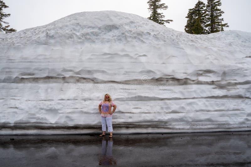 在夏天期间,逗人喜爱的白肤金发的旅游妇女姿势和立场在被犁的雪旁边一个大土墩在拉森国立公园加利福尼亚 免版税库存照片