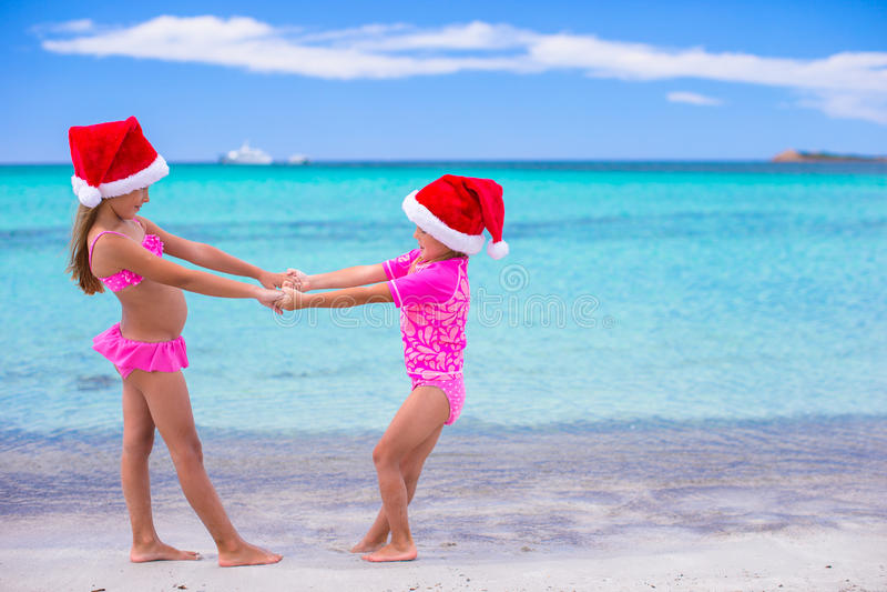 在夏天期间,圣诞老人帽子的小逗人喜爱的女孩 库存照片